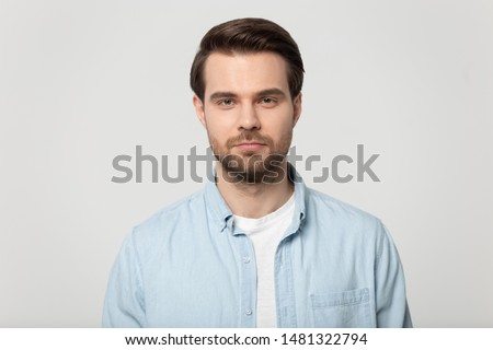 Close up head shot confident serious concentrated young man looking at camera studio portrait, isolated on grey white studio background. Thoughtful millennial guy posing for album photo.