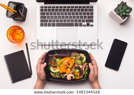 Lunch time. Grilled vegetables in take away box in woman hands for dinner in office, blank space on cellphone #1481344568