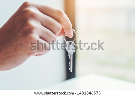 Sale Agent giving house keys to woman customer and sign agreement documents for realty purchase. #1481346575