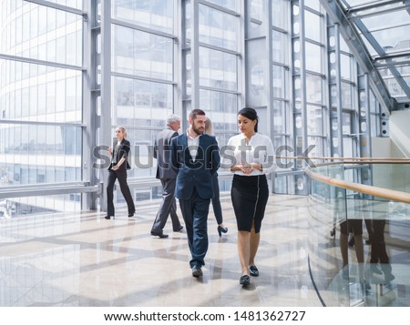 Business people walking in a modern hall of office building #1481362727
