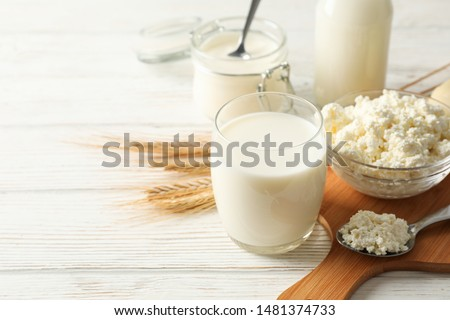Spikelets of wheat, dairy products and board on white wood background, copy space #1481374733