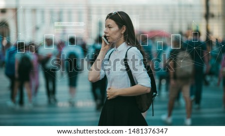 Facial recognition and search and surveillance of a person in the modern digital age, the concept. Young woman with phone in crowd of people on the street, identification and modern technology #1481376347