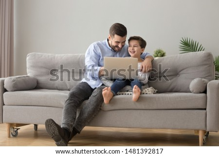 Young father and little son sitting on couch in modern cozy living room spend free time at home having fun using notebook laughing watching comedy funny movie, computer games online amusements concept #1481392817