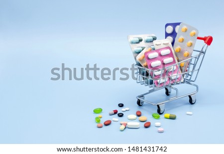 Buy and shopping medicine concept. Various capsules, tablets and medicine in shop trolley on a blue background. Creative idea for health care, health insurance and pharmaceutical company. Copy space. Royalty-Free Stock Photo #1481431742