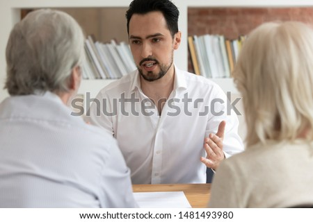 Serious male real estate agent talk with pensioner couple consulting about house property purchase or rent, man consultant or bank specialist speak help mature clients taking mortgage or loan Royalty-Free Stock Photo #1481493980