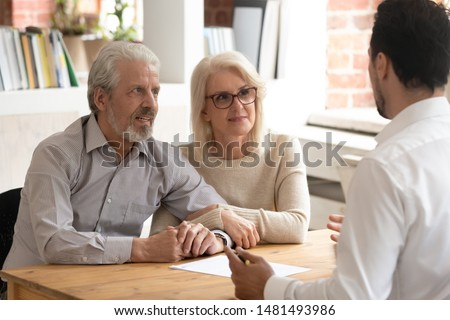 Happy mature couple meeting with male real estate agent or broker discuss future property purchase contract terms, excited pensioner husband and wife talk with financial consultant taking loan #1481493986