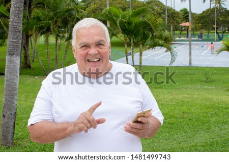 Fat old man searches with cellphone use in nature (mobile phone)