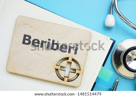 Writing note showing Beriberi. The text is written on a small wooden board with red cross silhouette. There are book, stethoscope, pen, blue table on the photo. #1481514479