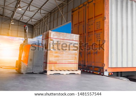 electric forklift pallet jack with cargo pallet shipment load into a truck #1481557544