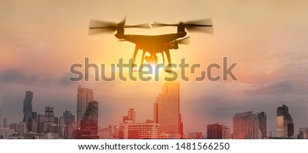 Drone quad copter with high resolution digital camera on the sky mountain and city background.