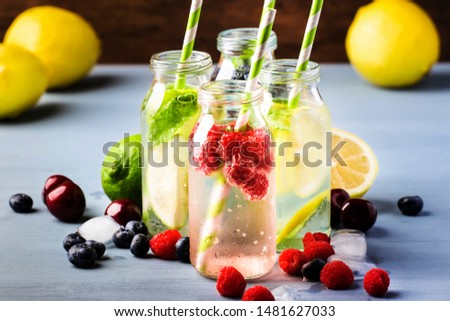 Berry, fruit and citrus non-alcoholic cold beverages and cocktails in glass bottles on blue background, copy space #1481627033