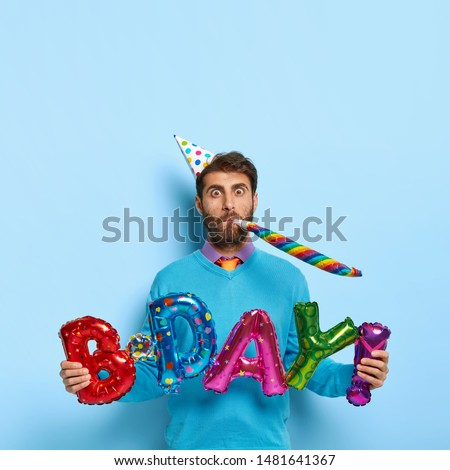 Funny Caucasian male blows in party horn, holds letter shaped balloons meaning birthday, wears festive paper hat and blue sweater, celebrates special occasion with friends, isolated on blue wall