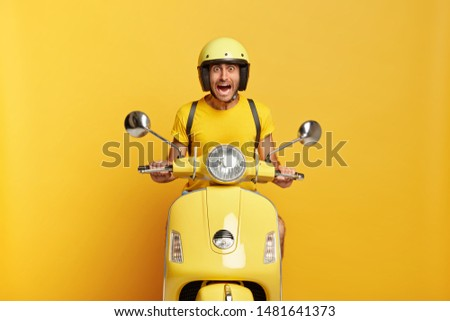 Scraed emotional driver poses on motorbike, drives long destination, has frightened look, screams from fear, wears yellow headgear, t shirt, carries rucksack on back, afraids of very high speed #1481641373