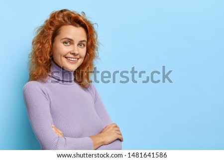 Sideways shot of beautiful carefree smiling woman with ginger hair, keeps arms folded, has happy expression, feels delighted after work, has natural beauty with no make up, poses on blue wall #1481641586