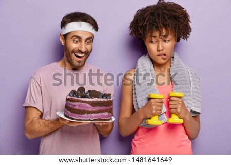 Unhappy Afro female temptates her will power, bites lips as looks at tasty baked cake in mans hands, keps to diet, works on loosing weight, stands with dumbbells and towel on neck. Sport, nutrition #1481641649