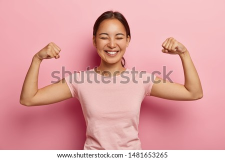 Strong powerful Asian woman with dark combed hair, toothy smile, raises arms and shows biceps, has piercing in ear, wears casual rosy t shirt, models against pink background. Look at my muscles! #1481653265