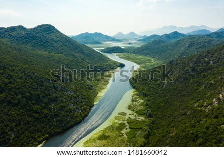 Aerial view of river Crnojevica leading to lake Skadar through a mountainous landscape. Lake Skadar National Park, Montenegro. #1481660042