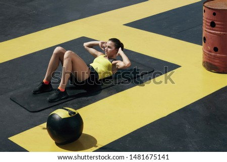 Fitness woman doing sit-ups exercise workout at gym. Sport girl exercising on yoga mat, doing abs crunches exercises outdoors at street #1481675141