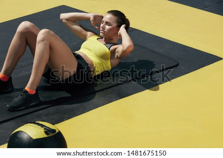 Fitness woman doing sit-ups exercise workout at gym. Sport girl exercising on yoga mat, doing abs crunches exercises outdoors at street #1481675150