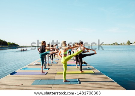 A big group of people attending yoga classes on a pontoon near the lake. #1481708303