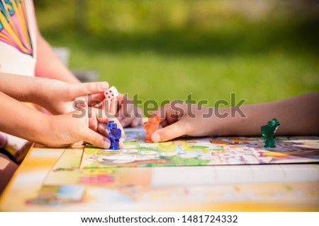 Board game and kids leisure concept. Kids are playing. people holding figures in hand. yellow, blue, green and red wood chips in children play.concept of board games. Dice, chips and cards. Party #1481724332