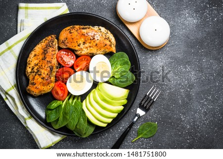 Keto diet plate on black background. HGrilled chicken breast, eggs, spinach, avocado and tomatoes. Top view. Royalty-Free Stock Photo #1481751800