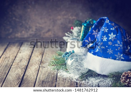 Christmas background with christmas balls, gift, Santa hat and snow on a wooden background #1481762912