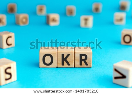 OKR - acronym from wooden blocks with letters, Objectives and Key Results OKR concept, random letters around, white  background #1481783210