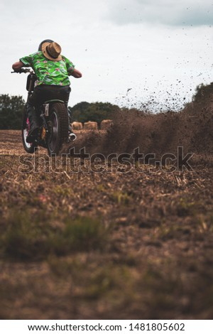 Stop motion picture of a dirt bike pulling of in a mud. Lifting a lot of dirt behind. Shallow depth of field. Coipy space for text.