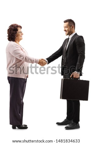Full length profile shot of a senior woman shaking hands with a young businessman with a briefcase isolated on white background Royalty-Free Stock Photo #1481834633