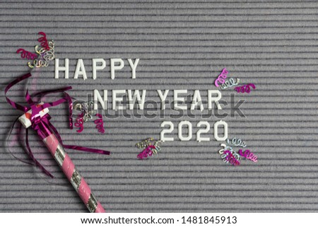 Happy New Year 2020 on grey felt ribbed letter board with white letters and pink confetti and noise maker