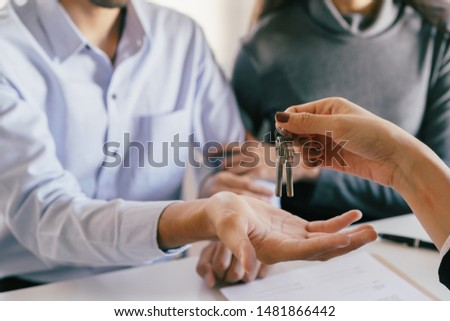 hand of Salespeople give keys to couples who are customer. Men are doing business in the office, business concept. #1481866442