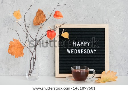 Happy Wednesday text on black letter board and bouquet of branches with yellow leaves on clothespins in vase on table Template for postcard, greeting card Concept Hello autumn Wednesday. Royalty-Free Stock Photo #1481899601