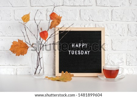 Happy Tuesday text on black letter board and bouquet of branches with yellow leaves on clothespins in vase on table Template for postcard, greeting card Concept Hello autumn Tuesday. #1481899604