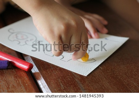Young boy use crayon painting elephant picture on wooden table by right hand