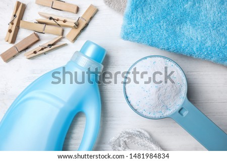 Flat lay composition with laundry detergents, clothespins and towels on white wooden background #1481984834