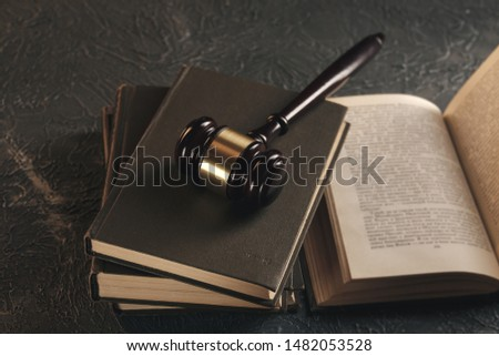 Law concept - Open law book with a wooden judges gavel on table in a courtroom or law enforcement office on blue background. #1482053528