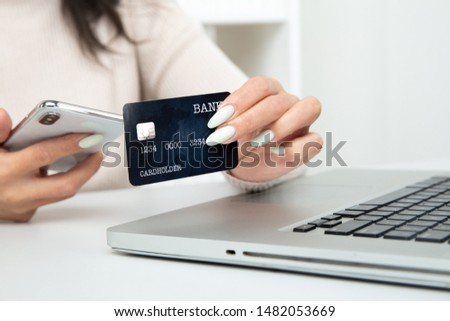 Beautiful woman holding card and using notebook to make online shopping. #1482053669