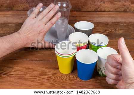 Disposable paper cups and plastic tableware on rustic table. Hand gestures approving to use disposable paper cups and renounce plastic tableware, concept #1482069668