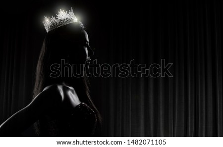 Portrait of Miss Pageant Beauty Contest in sequin Evening Ball Gown long dress with sparkle light Diamond Crown, silhouette low key exposure with curtain, studio lighting dark background dramatic Royalty-Free Stock Photo #1482071105