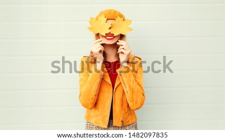 Autumn mood! happy smiling woman holding in her hands yellow maple leaves covering her eyes over gray wall background #1482097835