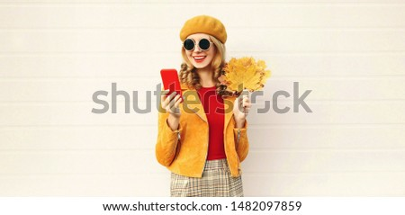 Autumn portrait smiling woman holding phone, yellow maple leaves wearing french beret on city street over gray wall background #1482097859
