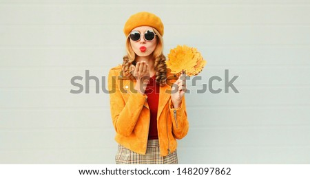 Autumn portrait woman with yellow maple leaves blowing red lips sending sweet air kiss over gray wall background #1482097862