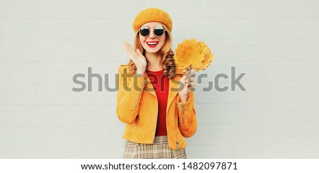 Autumn season! happy surprised woman with yellow maple leaves in french beret posing over gray wall background #1482097871