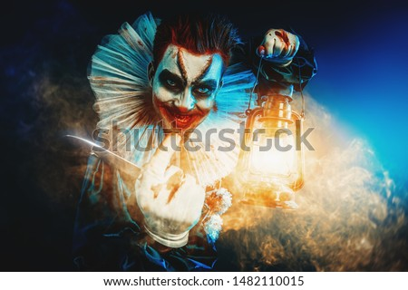 A portrait of an angry crazy clown from a horror film with a lantern. Halloween, carnival.