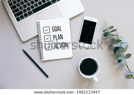 Goal, plan and action for 2020 on flat lay photo of workspace desk with smartphone, coffee, laptop and notebook with copy space background, minimal style and mockup concept  Royalty-Free Stock Photo #1482113447