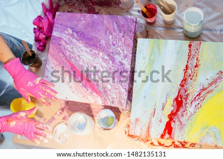 Close up of hands women painter finishing creating fluid acrylic abstract painting in art class, with a mess on the table full of bottle, jars with defferent paint colors. Art, design concept.