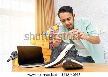 Asian man working taking photo to shoes with smart phone for post to sell online on the internet, Start up small business owner e-commerce ideas concept