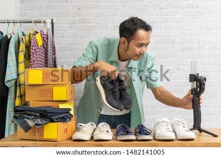 Asian man using smart mobile phone taking live selling shoes online, Recording making video blogger camera Start up small business owner e-commerce ideas concept #1482141005