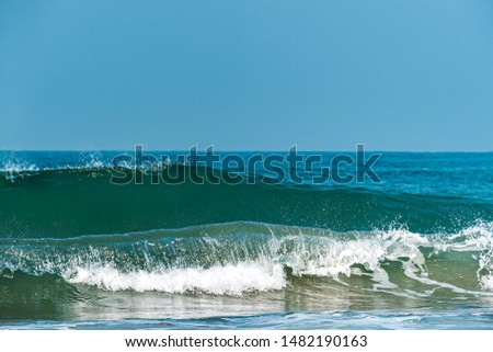Close up of sea waves isolated in blue background. Morning with clear sky picture of shining foamy ocean high tide in summer, tropical beach vacation design template.
